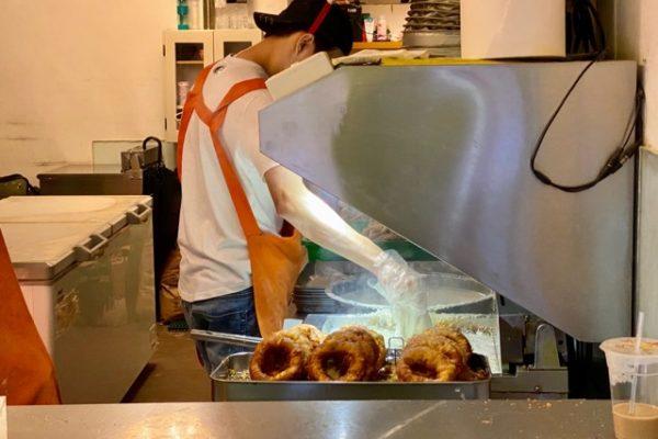 ドーナツを揚げている男性